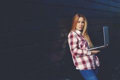 Freelancer de sexo femenino joven que usa el red-libro para el trabajo remoto durante tiempo libre Imágenes de archivo libres de regalías