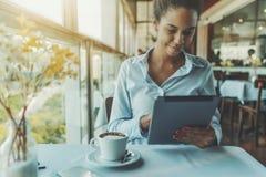 Freelancer de sexo femenino negro en restaurante con PC de la tableta Imagen de archivo libre de regalías
