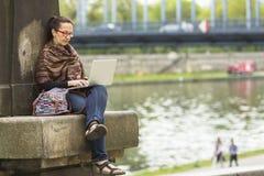 Freelancer de sexo femenino que se sienta al aire libre con el ordenador portátil Imagen de archivo