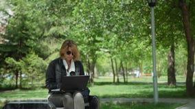 Freelancer de sexo femenino que trabaja al aire libre en día soleado almacen de metraje de vídeo