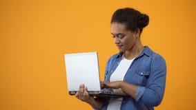 Freelancer de sexo femenino que trabaja en el ordenador portátil, mostrando la muestra aceptable, satisfecha con la conexión almacen de metraje de vídeo