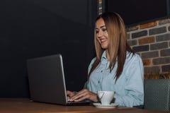 Freelancer de sexo femenino que trabaja en el ordenador portátil en un café imagen de archivo libre de regalías