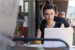 Freelancer de sexo femenino satisfecho que se sienta delante de un ordenador portátil Fotos de archivo libres de regalías