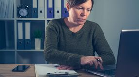 Freelancer de sexo femenino serio que trabaja en el ordenador portátil Imágenes de archivo libres de regalías