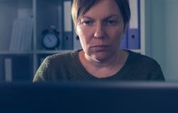 Freelancer de sexo femenino serio que trabaja en el ordenador portátil Fotos de archivo libres de regalías