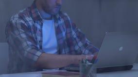 Freelancer de sexo masculino que mecanografía en el ordenador portátil detrás de la ventana lluviosa, periodista que trabaja en c almacen de video