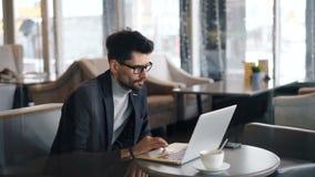 Freelancer de sexo masculino que trabaja en café usando el ordenador portátil que mira la pantalla que toca el teclado metrajes