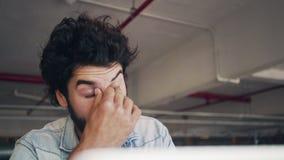 Freelancer de sexo masculino subrayado que usa el ordenador portátil en café almacen de video