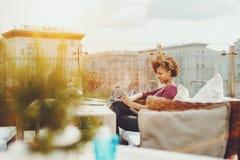 Freelancer del feemale del adolescente con el cojín digital al aire libre en café Fotografía de archivo