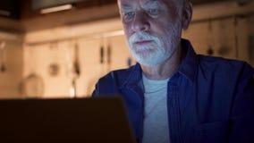 Freelancer del hombre mayor que usa el ordenador portátil en la noche de Ministerio del Interior Hombre de negocios con exceso de almacen de video