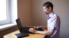 Freelancer die achter laptop werken stock footage