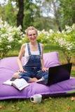 Freelancer die in de tuin werken Schrijven, die in Internet surfen Jonge vrouw die en pret op parkgebied ontspannen hebben die co royalty-vrije stock foto's