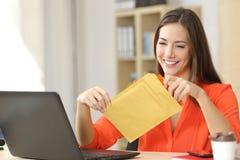 Freelancer die een opgevulde envelop openen stock afbeeldingen