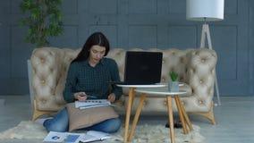 Freelancer die met grafieken en grafieken thuis werken stock videobeelden