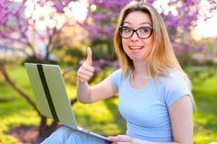Freelancer die met laptop werken en duimen in park tonen stock afbeeldingen