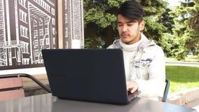 Freelancer do homem que senta-se no café e que trabalha no portátil video estoque