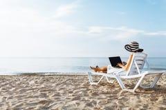 Freelancer dziewczyna pracuje na wakacje, przed pięknym morzem, siedzi z laptopem na oceanie, odizolowywający miejsce dla teksta zdjęcie royalty free