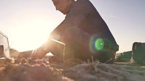 freelancer Equipaggi la siluetta che lavora alle free lance del computer portatile che si siedono sul sole di abbagliamento del s fotografie stock