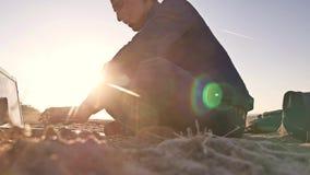 freelancer Equipaggi la siluetta di lavoro sulle free lance del computer portatile che si siedono sul sole di abbagliamento del s fotografia stock libera da diritti