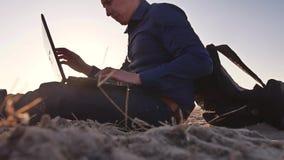 freelancer Equipaggi lavorare alle free lance del computer portatile che si siedono sulla siluetta del sole di abbagliamento del  immagine stock