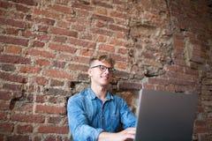 Freelancer experto del hombre alegre del inconformista que trabaja en el ordenador portátil en interior moderno imágenes de archivo libres de regalías