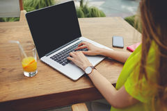 Freelancer fêmea criativo que senta o laptop dianteiro com For Your Information vazio da tela do espaço da cópia Fotografia de Stock