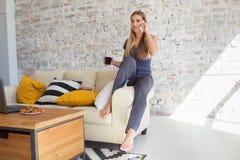 Freelancer fêmea em sua roupa home ocasional que trabalha remotly de sua mesa de jantar na manhã Casas em um sofá sobre Fotos de Stock Royalty Free