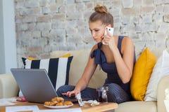 Freelancer fêmea em sua roupa home ocasional que trabalha remotly de sua mesa de jantar na manhã Casas em um sofá sobre Imagens de Stock Royalty Free