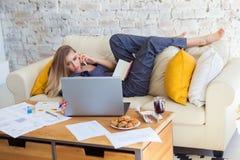 Freelancer fêmea em sua roupa home ocasional que trabalha remotly de sua mesa de jantar na manhã Casas em um sofá sobre Fotos de Stock