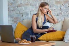 Freelancer fêmea em sua roupa home ocasional que trabalha remotly de sua mesa de jantar na manhã Casas em um sofá sobre Foto de Stock Royalty Free