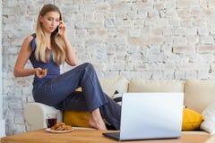 Freelancer fêmea em sua roupa home ocasional que trabalha remotly de sua mesa de jantar na manhã Casas em um sofá sobre Imagem de Stock