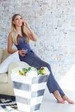 Freelancer fêmea em sua roupa home ocasional que trabalha remotly de sua mesa de jantar na manhã Casas em um sofá sobre Fotografia de Stock Royalty Free