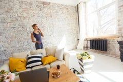 Freelancer fêmea em sua roupa home ocasional que trabalha remotly de sua mesa de jantar na manhã Casas em um sofá sobre Imagens de Stock