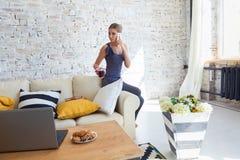 Freelancer fêmea em sua roupa home ocasional que trabalha remotly de sua mesa de jantar na manhã Casas em um sofá sobre Imagem de Stock Royalty Free