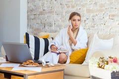 Freelancer fêmea em uma roupa branca do revestimento que trabalha remotly de sua mesa de jantar na manhã Casas em um sofá na Imagens de Stock Royalty Free