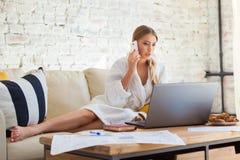 Freelancer fêmea em uma roupa branca do revestimento que trabalha remotly de sua mesa de jantar na manhã Casas em um sofá na Imagens de Stock