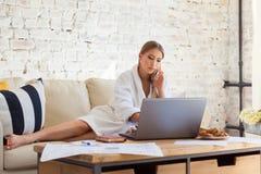 Freelancer fêmea em uma roupa branca do revestimento que trabalha remotly de sua mesa de jantar na manhã Casas em um sofá na Fotos de Stock