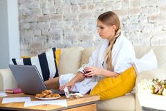 Freelancer fêmea em uma roupa branca do revestimento que trabalha remotly de sua mesa de jantar na manhã Casas em um sofá na Foto de Stock