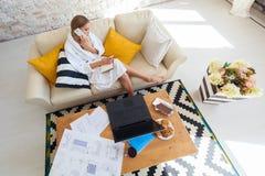 Freelancer fêmea em uma roupa branca do revestimento que trabalha remotly de sua mesa de jantar na manhã Casas em um sofá na Fotografia de Stock