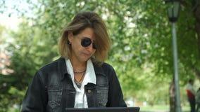 Freelancer fêmea maduro que trabalha em um parque da cidade vídeos de arquivo