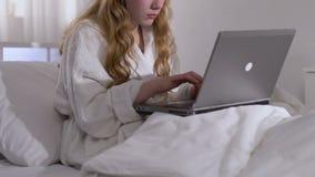 Freelancer fêmea no roupão que datilografa no portátil na cama, acesso remoto, trabalho filme