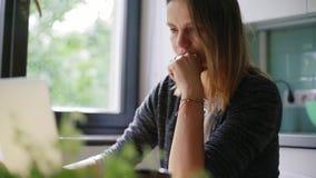 Freelancer för ung kvinna som hemifrån arbetar på frilans- skriva email på en bärbar dator lager videofilmer