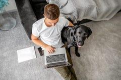 Freelancer facet siedzi w domu pracować z psem w uścisku, fotografia royalty free