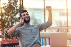 Freelancer farpado feliz entusiasmado que lê o e-mail com resultados sobre a vitória na competição em linha moderna que senta-se  imagens de stock