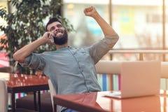 Freelancer farpado feliz entusiasmado que lê o e-mail com resultados sobre a vitória na competição em linha moderna que senta-se  foto de stock