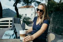 Freelancer feliz de la mujer joven en las gafas de sol que trabajan con el ordenador portátil i fotos de archivo