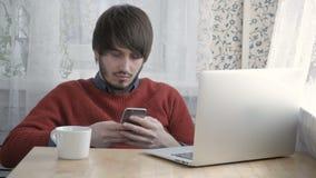 Freelancer feliz del hombre joven que trabaja con el ordenador portátil y el teléfono modernos en el café que toma la taza de caf