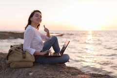 Be free, work whenever you want. Freelancer girl on the beach with her thumb up stock photos