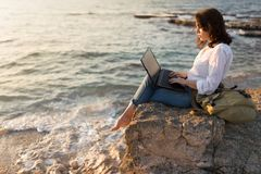 Be free, work whenever you want. Freelancer girl working on the beach royalty free stock image