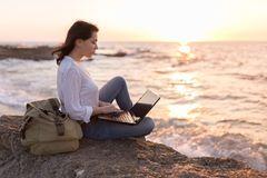 Be free, work whenever you want. Freelancer girl working on the beach stock image